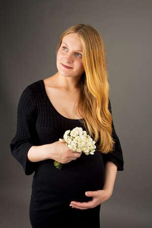 positiveness: pensando pregant joven rubia con flores aisladas sobre gris