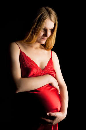 pretty young pregnant blonde in red nightshirt isolated on black Stock Photo - 5760202