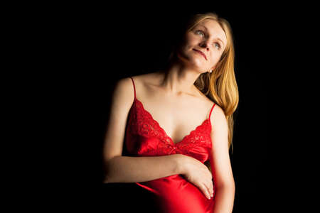 pretty young pregnant blonde in red nightshirt isolated on black photo
