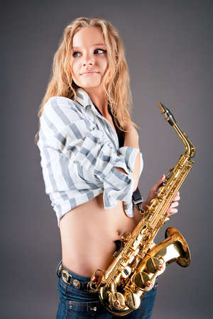 lifted hands: smiling dreaming young pretty blonde with sax isolated Stock Photo