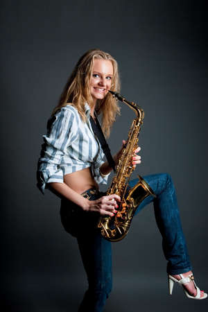 young smiling blonde saxophone player isolated over gray photo