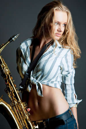 sexy young blonde saxophone player isolated over gray photo