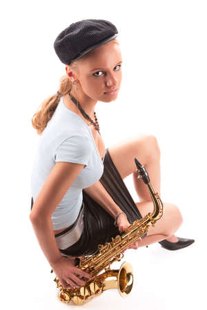 sensual blonde girl in cap sitting with saxophone isolated over white photo