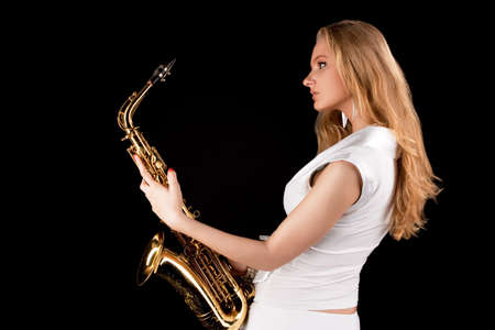 blonde girl with saxophone sansing in white dress half turned isoloated photo
