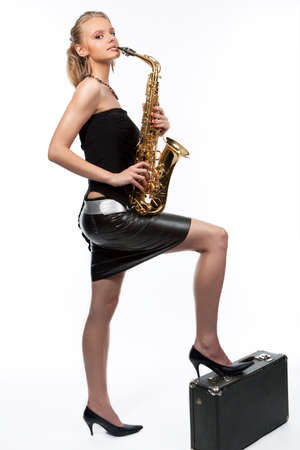 leather skirt: sensual pretty young blonde girl with saxophone and suiatcase isolated