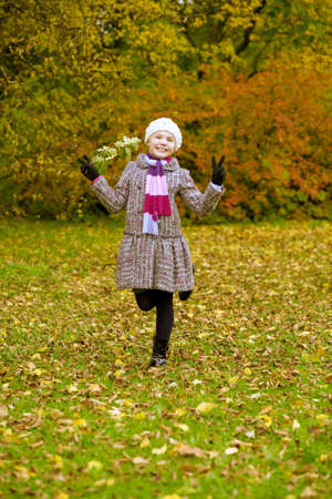 lifted hands: funny girl in coat having fun in autumn park with lifted hands and leg