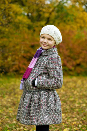 put forward: cute blonde little girl in modern coat standing smiling in autumn beautiful park