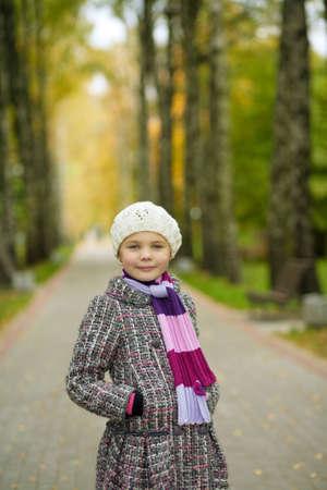 put forward: cute blonde little girl in modern coat standing in autumn beautiful park