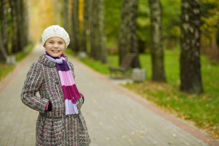 happy funny young blonde girl in autumn coat standing in park Stock Photo - 5907987
