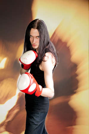readiness: gothic emo handsome man in boxing gloves isolated over grunge Stock Photo