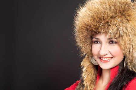 positiveness: sombrero aislado en negro de pieles de la bella joven de pelo oscura en invierno Foto de archivo