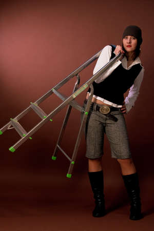 strives: extravagnt nice tall girl in winter cap carrying high ladder  Stock Photo