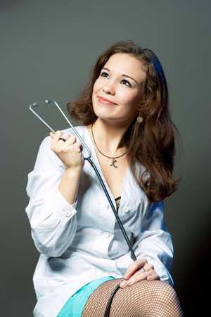endoscope: thinking young female caucasian doctor with endoscope smiling isolated over gray background