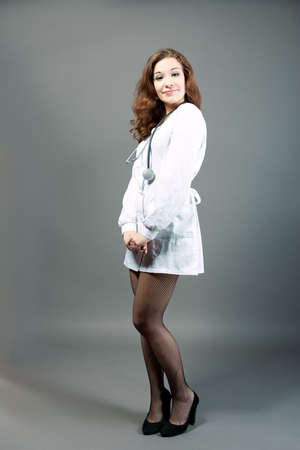 legs around: young sensual female doctor standing with smile in whites isolated over gray