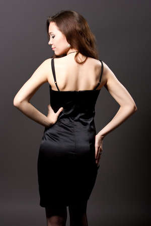 sexy back of young pretty caucasian girl in black dress isolated over gray background photo