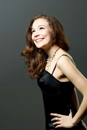 expressive funny smiling young girl in black evening dress isolated over gray photo