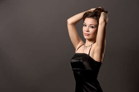 young sexy caucasian girl with relaxing face expression standing with hands lifted in black dress isolated over gray background photo