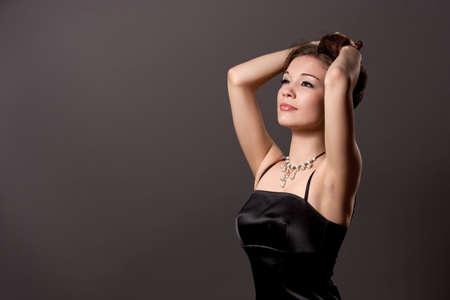 head tilted forward: young sexy caucasian girl with relaxing face expression standing with hands lifted in black dress isolated over gray background