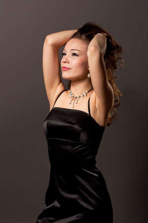 head tilted forward: young sexy caucasian girl with  dreaming face expression standing with hands lifted in black dress isolated over gray background