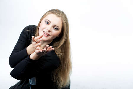 lifted hands: young pretty caucasian blond sitting with hands lifted in front sending kiss isolated over white Stock Photo