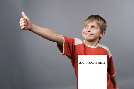 young caucasian teenager boy with identity plate and hand lifted with thumbs up isolated over gray background photo