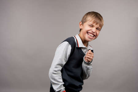 positiveness: pretty and cute laughing boy with extraordinary positive facial expression making grimace isolated on gray background Stock Photo