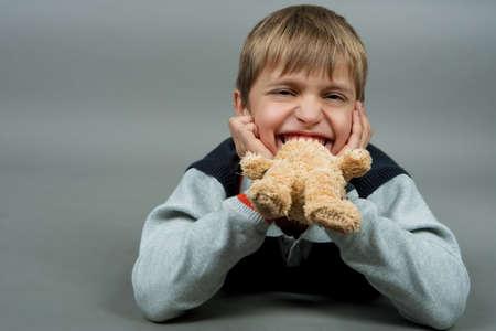 positiveness: j�venes teenagre lindo con osito de peluche en boca riendo y sentar en piso aislado sobre gris