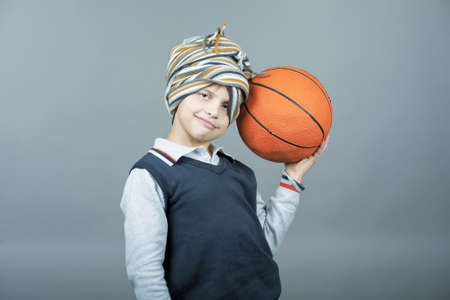 tenager: young and funny caucasian tenager boy holding basketball ball near head and having fun with scarf around head standing isolated on gray background Stock Photo
