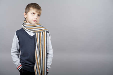 positiveness: young and patient caucasian teenager elegant boy standing with hands in pockets and wearing coloful long scarf with calm look standing isolated over gray background with copyspace