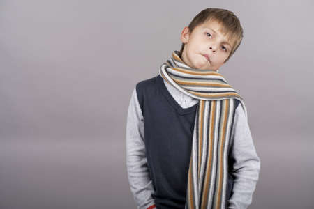 funny cute caucasian blond boy making grimace with colorful scarf standing isolated over gray background photo