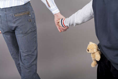 nearness: young and careful father together with his teenager son holding hands of each other standing isolated over gray background with teddy bear