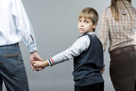young caucasian family standing together with young teen boy in middle looking backwards with sad facial expression isolated over gray background Stock Photo - 6737277