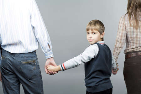 nearness: young caucasian family together with young teenager boy in middle turned backwards with smile and isolted over gray background Stock Photo