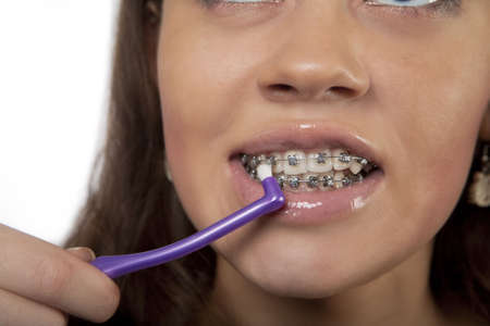 exploring brackets while using round toothbrush for young dark hair girl isolated over white