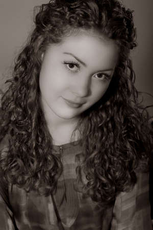 portrait closeup of young pretty caucasian girl with nice natural curly hair sitting isolated with tilted head