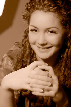 young pretty smiling caucasian girl with natural beautiful curly hair sitting in front of wall and laughing made in sepia tonality
