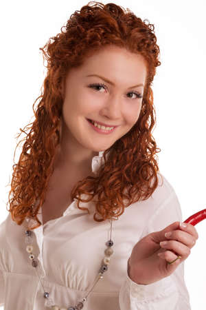 haired: smiling and happy caucasian red haired girl with curly hair holding chilly pepper and having fun isolated on white background