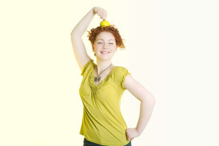 underwaist: caucasian girl making an exercise with green nice apple and holding it on head with great pleasure smiling  nicely and isolated over white background Stock Photo