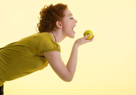 underwaist: brave looking young caucasian girl making a bite on green apple standing on half-face and isolated Stock Photo