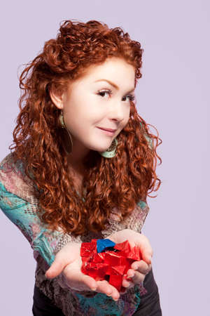 red haired expressive young girl offering blue and red candies standing with smiling curious look and body shaped isolated Stock Photo - 7539774