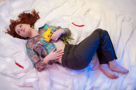 young caucasian girl lying over white linen and hair spread over the floor with relaxing dreaming look and some pepper pods around photo