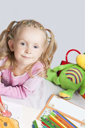smiling and happy young caucasian small girl with plenty of colorful pencils lying on florr and drawing with positive facial expression photo