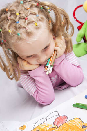 young little caucasian girl dreaming on her color picture figuring out a right choice with colorful pencils