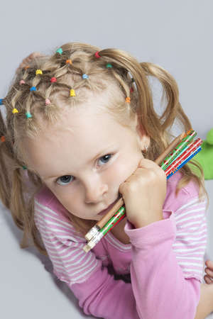 litle: serious looking young litle blond caucasian girl holding color pencils in hand and lying on floor with concentrated look isolated