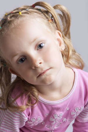 young blond caucasian child with sad look and long hair tails sitting with tilted head isolated photo