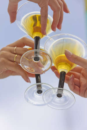 three female hands holding wineglasses with white wine over blue sky background. shot with studio strobe on location.