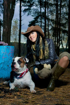 bright young caucasian brunette girl in forest with her lovely big dog and having good time together.  photo
