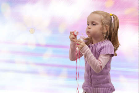 cute young little blond girl making soap bubbles and having rest. isolated over colorful  background photo