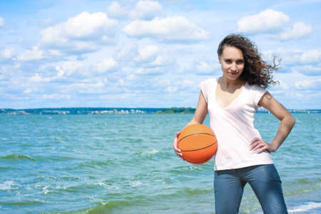 positiveness: sporty and slim caucasian girl with curly natural hair holding orange ball near seaside Stock Photo
