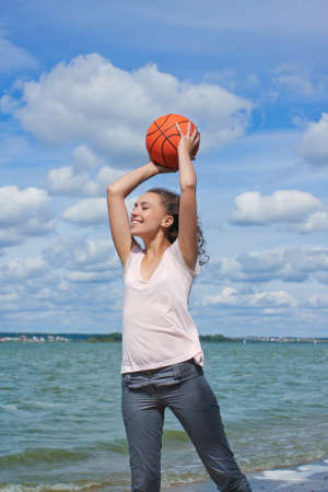 roaring sea: sporty and slim caucasian girl with curly natural hair holding orange ball near seaside Stock Photo